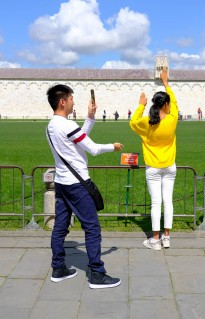 Tourists having fun holding up the leaning tower of Pisa